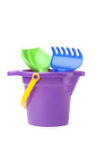 Toy purple bucket with spade and rake Royalty Free Stock Photography