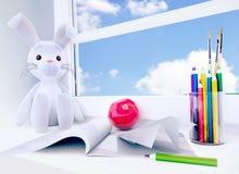 Toy rabbit, apple, album, paper plane, pencils on the wi Stock Photo