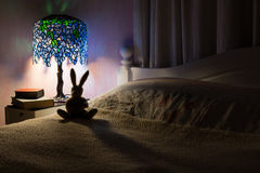 Toy rabbit back lit by Tiffany lamp in bedroom. Bedroom interior at night. A dark room illuminated by a Tiffany style lamp silhouetting a toy rabbit. Story time stock photography