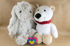 Toy rabbit and bear on a craft paper table with a hearts on Vale Royalty Free Stock Photo