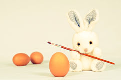 Toy rabbit with eggs and painting brush Stock Images