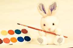 Toy rabbit with paints Royalty Free Stock Photography