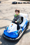 Toy racing car. A little boy sitting on a toy racing car Stock Image