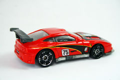 Toy racing car. A red toy racing car, number 75 on a white background Stock Photography