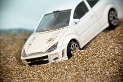 Toy racing car crashed into a sand-dune and slips. Model of white race car in the sand dunes Stock Image