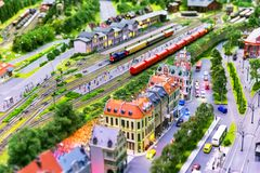 Toy railway layout. Macro view of toy hobby railroad layout with railway station building, passenger and freight cargo trains on rail tracks Royalty Free Stock Photo