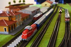 Toy railway station with trains. Toy railway station with 3 trains, railroads, station building. Miniature railstation mock-up that represents a real life stock images