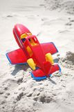 Toy red airplane laying in the sand Royalty Free Stock Image