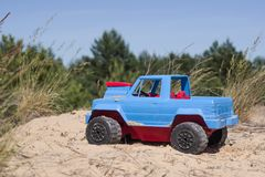Toy red blue pickup in the sand of a green forest background. Colorful toy truck Stock Photos
