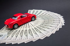 Toy red car on dollars Stock Photos