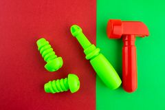 Toy red hammer and green screwdriver. Toy red hammer and green screwdriver on a red paper background royalty free stock photos