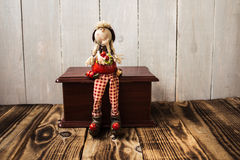 Toy redhood sitting on wooden box Royalty Free Stock Photo