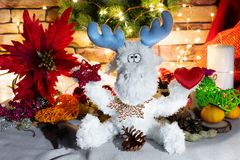 Toy reindeer with stars in hands, tangerins, cookies and bright star shape bokeh stock images