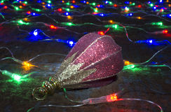 Toy rests upon festoon of the colour lights. On dark background Stock Images