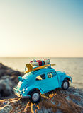 Toy retro car on rock by the sea Royalty Free Stock Photos