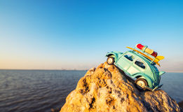 Toy retro car on rock by the sea Stock Photo