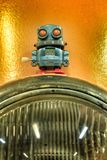 Toy robot on front vintage light of car stock photo