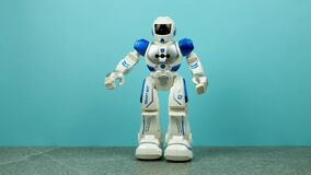 A toy robot walks by. The robot is on a tile with a wall of blue behind it. The robot is blue in color and has red