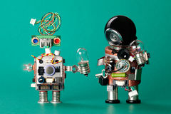 Toy robots with lamp bulbs. Circuits chip handyman characters, funny black helmet head, electric wire hairstyle colored Royalty Free Stock Photography