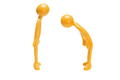 Toy rubber figurine bowing to another Royalty Free Stock Photo