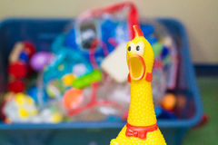 Toy rubber shriek yellow chicken on blur toy background in messy Royalty Free Stock Images
