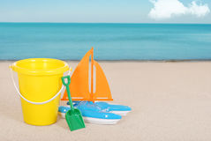 Toy Sailboat and childs bucket on the beach Stock Image