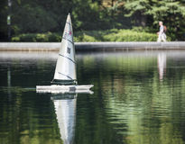 Toy Sailboat on the Conservatory Water in Central Park, New York City. A small white toy sailboat makes its way across the Conservatory Water pond in Central Stock Photo