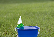 Toy sailboat floating in a bucket stock images