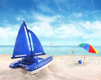 Toy sailboat in sand with beach scene Stock Photos