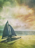 Toy sailboat in sand with vintage look. Toy sailboat in the sand with vintage look Royalty Free Stock Photos