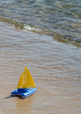 Toy sailboat at waters edge Royalty Free Stock Photo