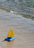 Toy sailboat at water's edge Royalty Free Stock Photo