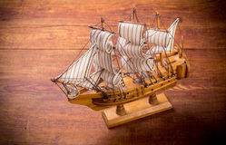 Toy sailboat on a wooden background Royalty Free Stock Images