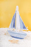 Toy sailing boat and seashells on yellow background Royalty Free Stock Photo