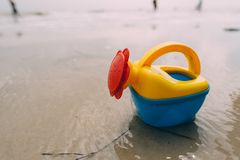 Toy sand bucket bright blue on beach. Close up stock images