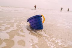 Toy sand bucket bright blue on beach. Close up royalty free stock photography
