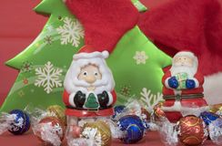 Toy santa with candy. Tabletop festive christmas holiday scene close-up of small candy filled toy santa claus and clauses in front of a green paper christmas Royalty Free Stock Photos
