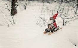 Toy Santa Claus auf einem Schlitten in einem schneebedeckten Wald Stockbilder