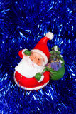 Toy Santa Claus in blue tinsel. New Year Royalty Free Stock Photography