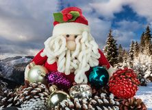 Toy Santa Claus with Christmas decorations on a background of mountains covered with forest royalty free stock photos