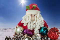 Toy Santa Claus with Christmas decorations on the background of a winter landscape with bright sunshine. Christmas and New Year gr stock photography