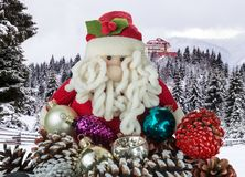 Toy Santa Claus with Christmas decorations on the background of a winter landscape with a snow-covered forest in the mountains and stock photos