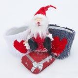 Toy Santa Claus con los regalos en la nieve El concepto de la Navidad y de Año Nuevo Caja y tazas de regalo con los corazones Fotos de archivo libres de regalías