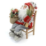 Toy Santa Claus. Santa Claus doll on a bench with a bag of gifts royalty free stock photos