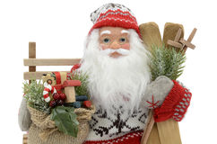 Toy Santa Claus. Santa Claus doll on a bench with a bag of gifts royalty free stock images