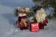 Toy Santa Claus et bonhomme de neige avec un cadeau sur la neige Images stock