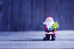 Toy santa claus keeps the felled tree, over blue wooden backgrou Royalty Free Stock Photo