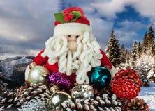 Toy Santa Claus met Kerstmisdecoratie op een achtergrond van bergen met bos worden behandeld dat royalty-vrije stock foto's