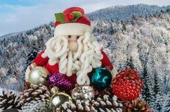 Toy Santa Claus met Kerstmisdecoratie tegen de achtergrond van een de winterlandschap met bergen met bossen worden behandeld dat stock fotografie