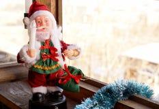 Toy Santa Claus mit einer Kerze in einer Hand Lizenzfreie Stockfotografie